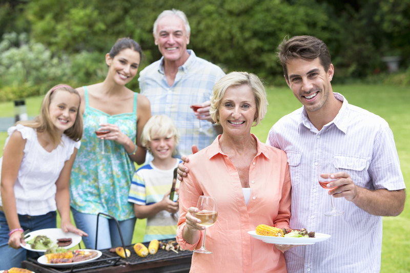 Portrait of happy multi-generation family enjoying barbecue and wine